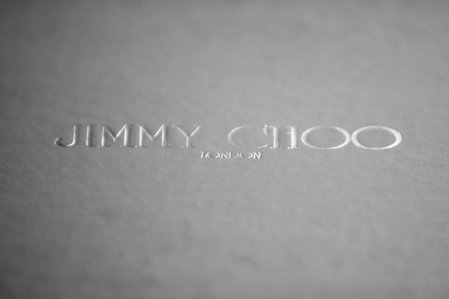 A back and white photograph showing the Jimmy Choo branding on the shoebox containing a bride